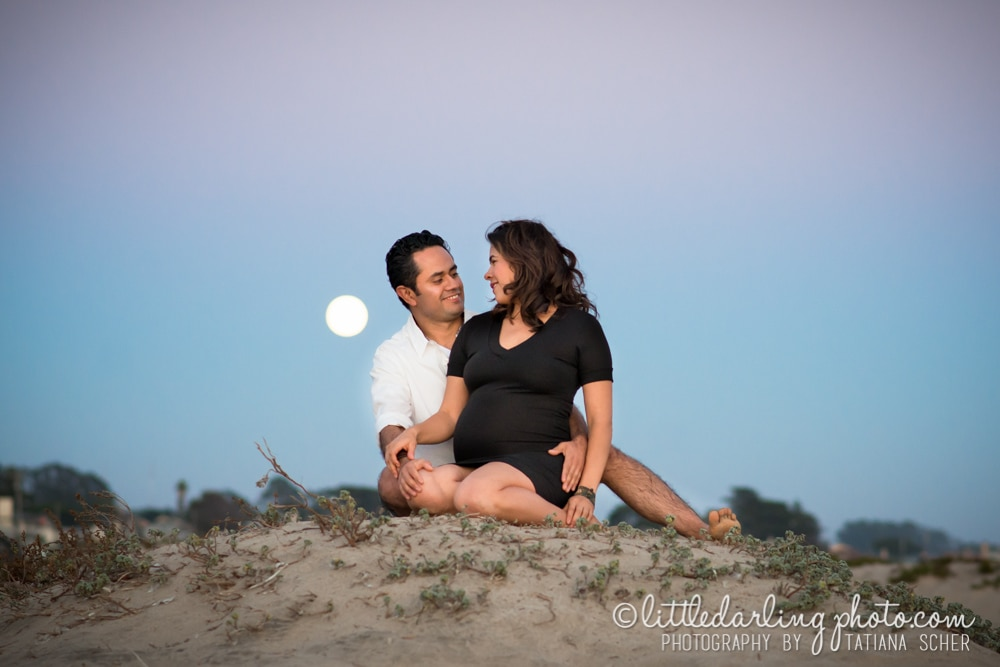 Pregnant couple with the full moon as background